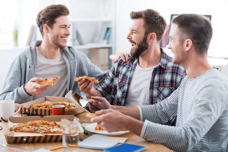 Foto de We work hard but have fun doing it! Three happy young men eating pizza together while sitting in the office - Imagen libre de derechos