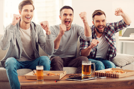 Photo pour Domestic fans. Three happy young men watching football game and keeping arms raised while sitting on sofa - image libre de droit
