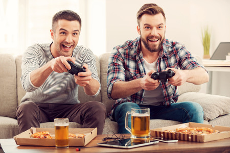 Photo pour The avid gamers. Two young happy men playing video games while sitting on sofa - image libre de droit