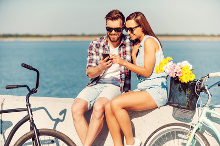 Foto de Look at this picture! Smiling young couple looking at mobile phone while sitting outdoors near their bicycles - Imagen libre de derechos