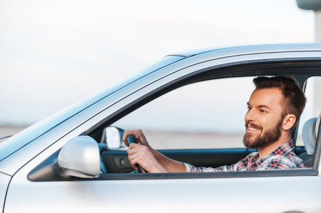 Photo for Riding his new car. Side view of handsome young man driving his car and smiling - Royalty Free Image