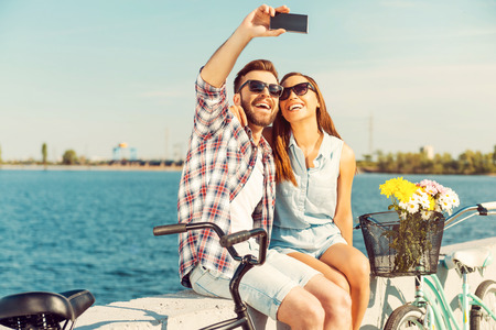 Photo for Collecting the bright moments. Smiling young couple making selfie while sitting on parapet near their bicycles - Royalty Free Image