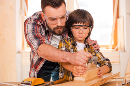 Foto de Success is a learnable skill. Concentrated young male carpenter teaching his son to work with wood in his workshop - Imagen libre de derechos