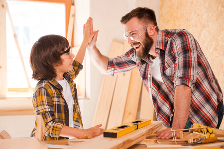Photo for We did it! Cheerful young male carpenter and his son giving high-five to each other while working in workshop - Royalty Free Image