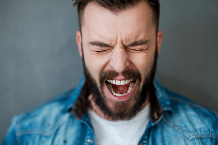 Foto de Unleashed emotions. Frustrated young man keeping eyes closed and mouth opened while standing against grey background - Imagen libre de derechos