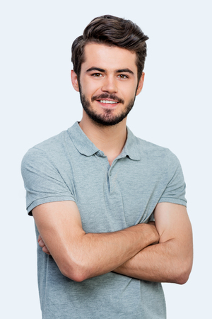 Photo for Candid smile. Handsome young man keeping arms crossed and looking at camera while standing against white background - Royalty Free Image