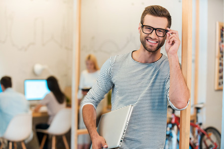 Photo for Confident IT professional. Cheerful young man carrying laptop and adjusting his eyeglasses while his colleagues working in the background - Royalty Free Image