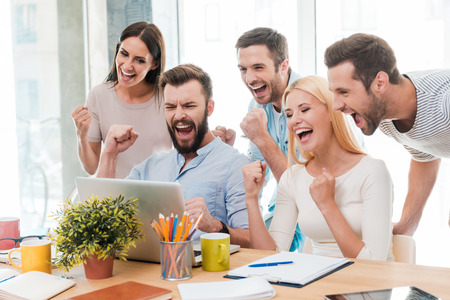 Photo for Everyday winners. Group of happy business people in smart casual wear looking at the laptop and gesturing - Royalty Free Image