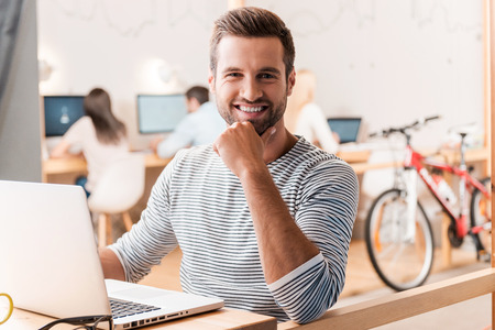 Photo for Enjoying his work. Handsome young man looking at camera and smiling while his colleagues working in the background - Royalty Free Image