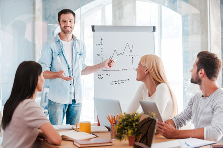 Foto de Discussing company progress. Confident young man standing near whiteboard and pointing graph while his colleagues sitting at the desk - Imagen libre de derechos