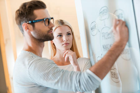 Foto de Planning is a key to success. Confident young man sketching on whiteboard while woman standing close to him and holding hand on chin - Imagen libre de derechos