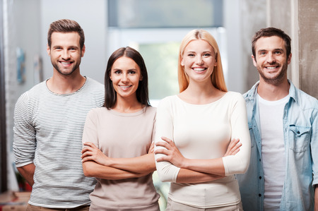 Photo for Young and successful team. Four young business people in smart casual wear standing close to each other and smiling discussing - Royalty Free Image