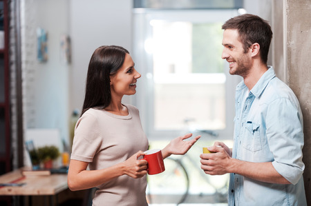 Foto per Spending a nice coffee break. Two cheerful young people holding coffee cups and talking while standing in office - Immagine Royalty Free