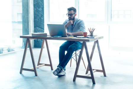 Photo for Feeling comfortable at his working place. Concentrated young beard man working on laptop while sitting at his working place in office - Royalty Free Image