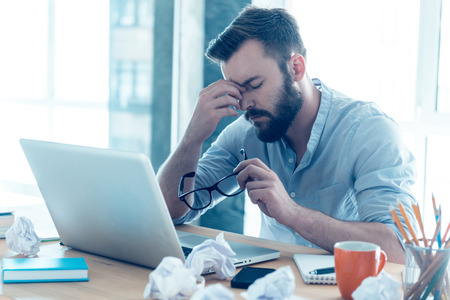 Foto de Feeling exhausted. Frustrated young beard man massaging his nose and keeping eyes closed while sitting at his working place in office - Imagen libre de derechos