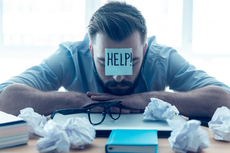 Foto de He needs help. Hopeless young beard man with adhesive note on his forehead leaning at the desk and keeping eyes closed while sitting at his working place in office - Imagen libre de derechos