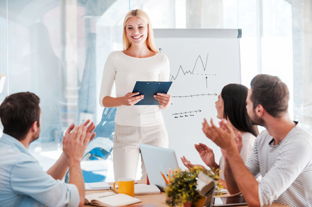 Photo for Great presentation! Cheerful young woman standing near whiteboard and smiling while her colleagues sitting at the desk and applauding - Royalty Free Image