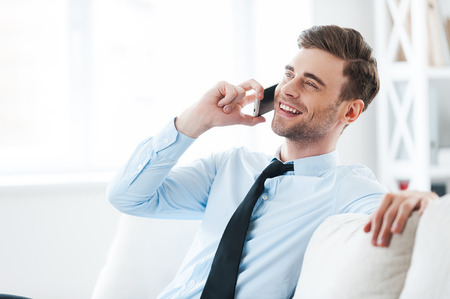 Foto de It is great to hear from you! Cheerful young businessman talking on the mobile phone and smiling while sitting on sofa - Imagen libre de derechos