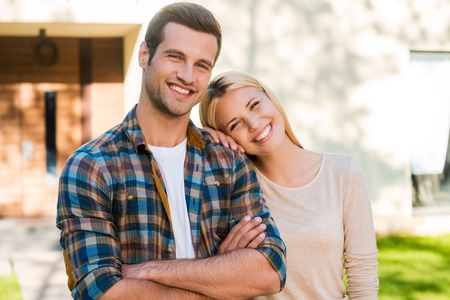 Photo pour Happy young couple. Happy young couple bonding to each other and smiling while standing against their new house - image libre de droit