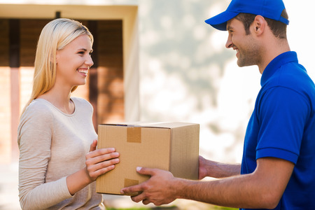 Foto de It always arrives in time. Side view of happy young delivery man giving a cardboard box to young woman while standing in front of the house - Imagen libre de derechos