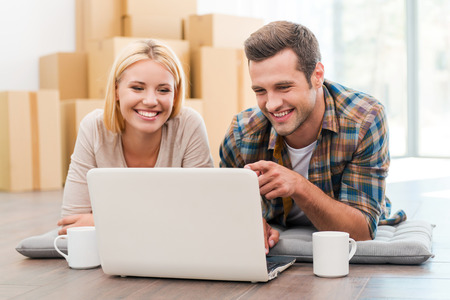 Foto de In search of a good moving company. Cheerful young couple laying on the floor of their new apartment and looking at laptop while cardboard boxes laying in the background - Imagen libre de derechos