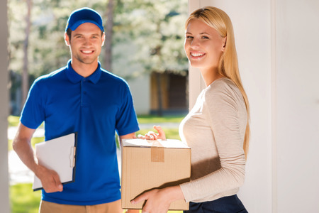 Foto de First class delivery service. Beautiful young woman holding a cardboard box while young delivery manholding clipboard and smiling - Imagen libre de derechos