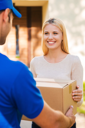 Foto de Delivery from hands to hands. Beautiful young woman smiling while young delivery man giving a cardboard box to her - Imagen libre de derechos