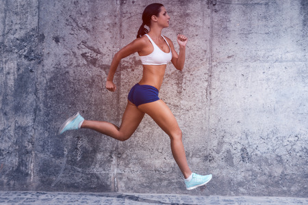 Photo for Keep on running.  Full length side view of beautiful young woman in sports clothing running with a concrete wall in the background - Royalty Free Image