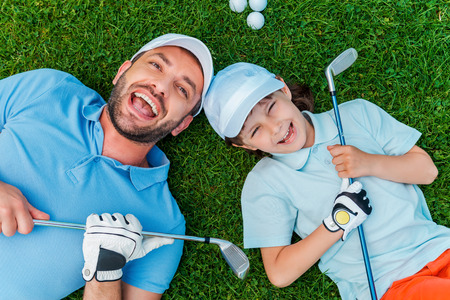 Foto de Happy golfers. Top view of cheerful little boy and his father holding golf clubs and smiling while lying on the green grass - Imagen libre de derechos
