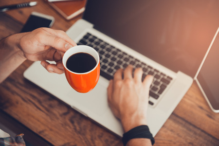 Foto de Fresh coffee for great ideas. Top view ofman working on laptop and holding cup of coffee while sitting at his working place - Imagen libre de derechos