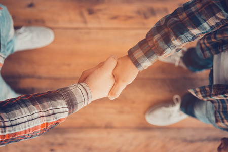 Photo pour Men shaking hands. Top view of two men shaking hands while standing on the wooden floor - image libre de droit