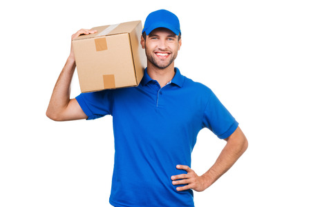 Photo for Confident delivery man. Joyful young courier carrying cardboard box on shoulder and smiling while standing against white background - Royalty Free Image
