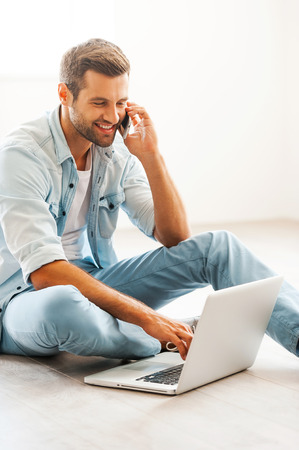 Photo for Doing business at home. Smiling young man working on laptop and talking on the mobile phone while sitting on the floor at his apartment - Royalty Free Image