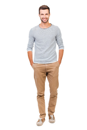 Foto de Confident and stylish. Full length of cheerful young man holding hands in pockets and looking at camera while standing against white background - Imagen libre de derechos
