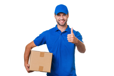 Photo for The best delivery service. Cheerful young courier holding a cardboard box and showing his thumb up while standing against white background - Royalty Free Image