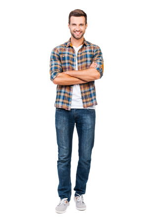 Photo pour Reliable guy. Full length of smiling young man keeping arms crossed and looking at camera while standing against white background - image libre de droit