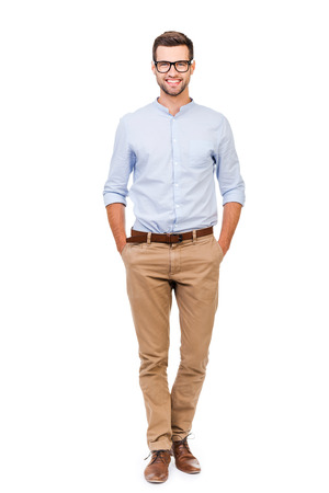 Photo pour Confident in any situation. Happy young man holding hands in pockets and looking at camera while standing against white background - image libre de droit