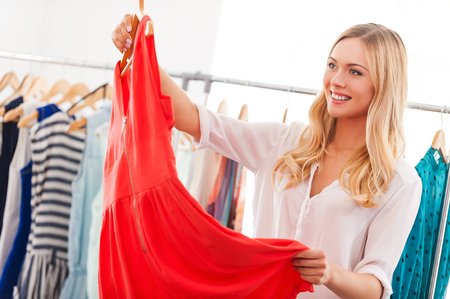 Photo pour I like this dress! Smiling young woman holding dress and smiling while standing in clothing store - image libre de droit