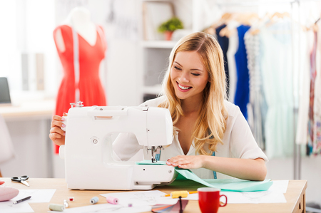 Photo pour Creating new fashionable styles. Cheerful young woman sewing while sitting at her working place in fashion workshop - image libre de droit