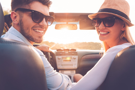 Foto de Our perfect weekend journey. Rear view of cheerful young couple looking over shoulder and smiling while sitting inside of their convertible - Imagen libre de derechos