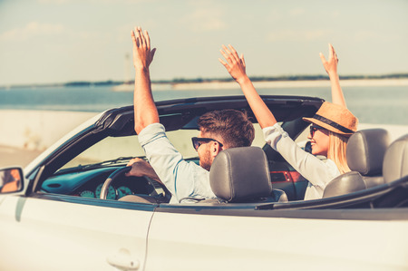 Foto de Perfect start of their weekend. Excited young couple keeping arms raised while riding in their white convertible - Imagen libre de derechos