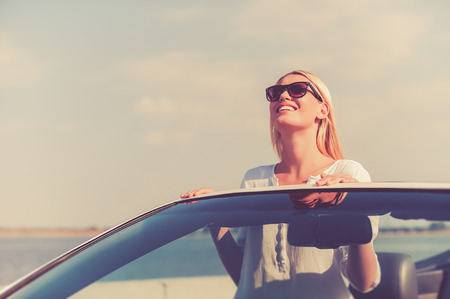 Photo for Feeling freedom. Beautiful young woman in eyewear enjoying road trip while standing up in white convertible - Royalty Free Image