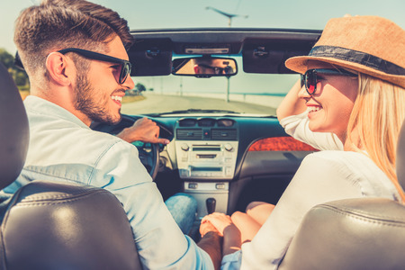 Photo pour Enjoying their road trip. Side view of cheerful young couple holding hands and looking at each other while sitting inside of their convertible - image libre de droit