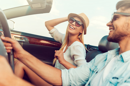 Photo for Having fun along the way. Beautiful young woman smiling and adjusting her hat while her boyfriend sitting near and driving convertible - Royalty Free Image