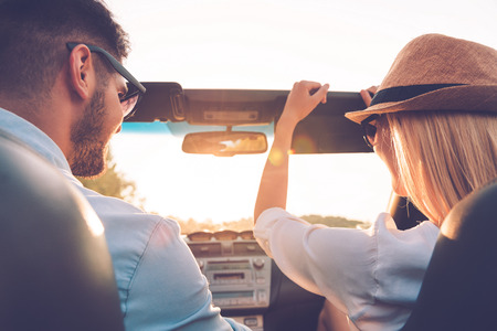 Foto de Enjoying road trip together. Rear view of joyful young couple having fun while riding in their convertible - Imagen libre de derechos