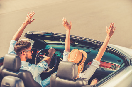 Foto de Getting away from it all. Top view of cheerful young couple keeping arms raised while riding in their white convertible - Imagen libre de derechos