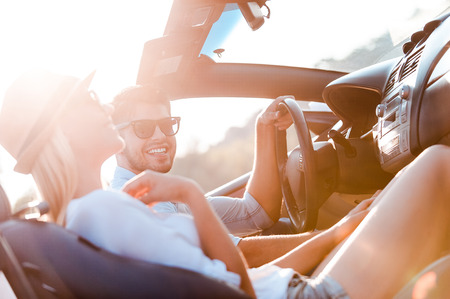 Photo for The greatest day for the road trip. Happy young couple smiling while sitting inside of their convertible - Royalty Free Image
