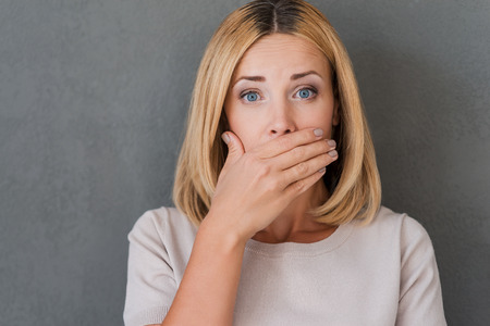 Photo pour Shocking news. Surprised mature woman covering mouth with hand and staring at camera while standing against grey background - image libre de droit