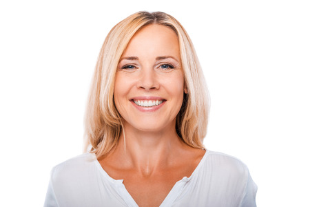 Foto de Cheerful mature woman. Portrait of happy mature woman looking at camera and smiling while standing against white background - Imagen libre de derechos