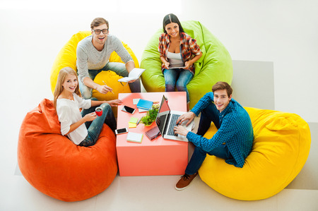 Photo for Creative work space. Top view of four cheerful young people working together and looking up while sitting at the colorful bean bags - Royalty Free Image